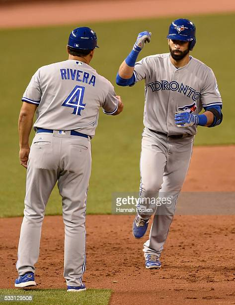 Third base coach Luis Rivera of the Toronto Blue Jays congratulates Jose Bautista on threerun home run against the Minnesota Twins during the sixth...