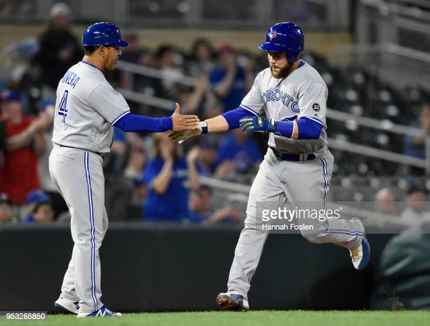 Third base coach Luis Rivera of the Toronto Blue Jays congratulates Russell Martin on a solo home run against the Minnesota Twins during the fifth...