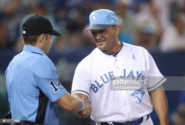 Third base coach Luis Rivera of the Toronto Blue Jays greets home plate umpire Mark Wegner as he delivers the lineup card before the start of MLB...