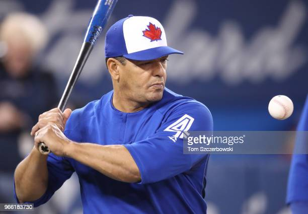 Third base coach Luis Rivera of the Toronto Blue Jays hits grounders with a fungo bat during batting practice before the start of MLB game action...