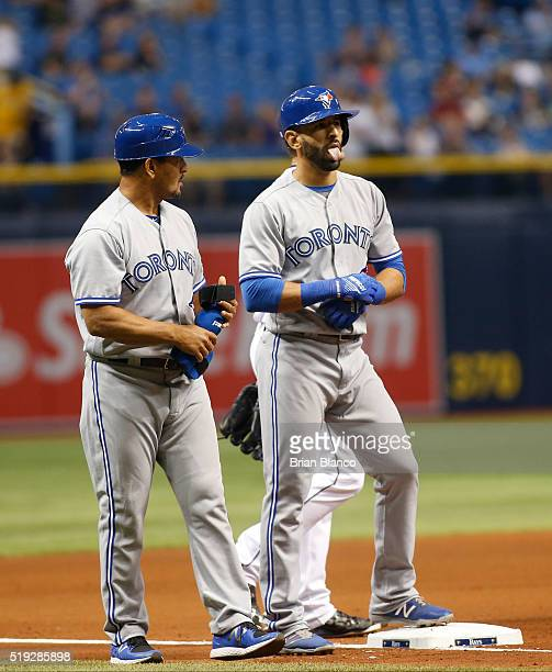 Third base coach Luis Rivera of the Toronto Blue Jays looks on as Jose Bautista reacts after hitting a triple to deep right field during the fourth...