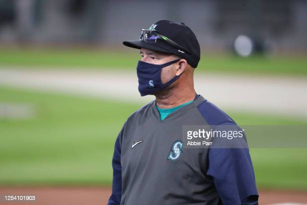 Third Base Coach Manny Acta of the Seattle Mariners looks on while wearing a face covering during summer workouts at T-Mobile Park on July 03, 2020...