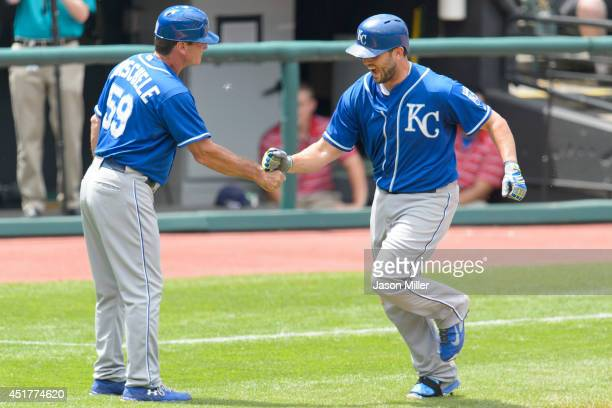 Third base coach Mike Jirschele celebrates with Mike Moustakas of the Kansas City Royals as Moustakas rounds the bases after hitting a solo homer run...
