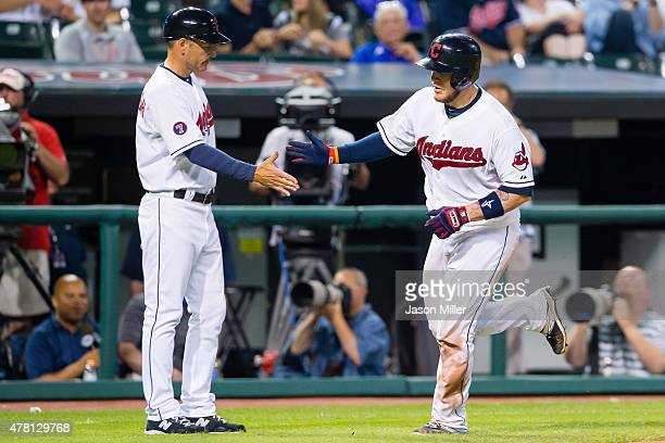 Third base coach Mike Sarbaugh celebrates with Roberto Perez of the Cleveland Indians as Perez round the bases after hitting a solo home run during...