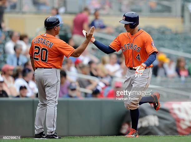 Third base coach Pat Listach of the Houston Astros congratulates George Springer on a solo home run against the Minnesota Twins as Springer rounds...