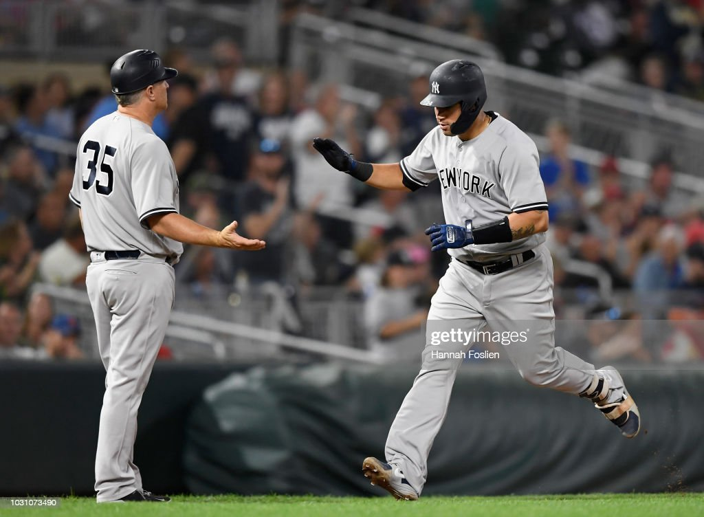 Third base coach Phil Nevin #35 of the New York Yankees congratulates Gary Sanchez #24 on a solo home run against the Minnesota Twins during the sixth inning of the game on September 10, 2018 at Target Field in Minneapolis, Minnesota.