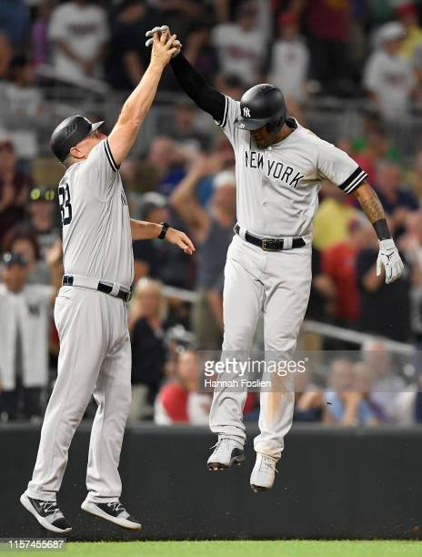 Third base coach Phil Nevin of the New York Yankees congratulates Aaron Hicks on a tworun home run against the Minnesota Twins during the ninth...