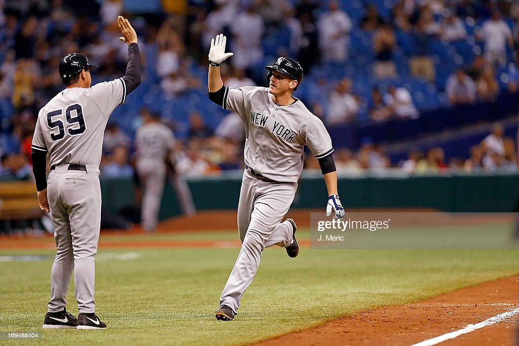 Third base coach Rob Thomson #59 of the New York Yankees congratulates Lyle Overbay #55 after his eleventh inning home run that turned out to be the game winner against the Tampa Bay Rays at Tropicana Field on May 25, 2013 in St. Petersburg, Florida.