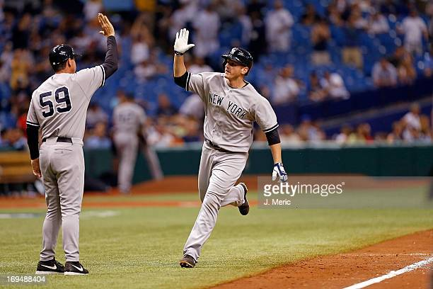 Third base coach Rob Thomson of the New York Yankees congratulates Lyle Overbay after his eleventh inning home run that turned out to be the game...