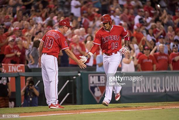 Third base coach Ron Roenicke and Jefry Marte of the Los Angeles Angels of Anaheim celebrate as Marte runs the bases after hitting a grand slam...