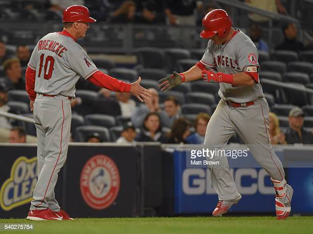 Third base coach Ron Roenicke and Mike Trout of the Los Angeles Angels of Anaheim highfive as Trout runs the bases after hitting a solo home run...