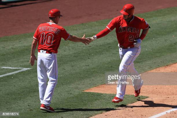 Third base coach Ron Roenicke congratulates CJ Cron of the Los Angeles Angels of Anaheim after hitting a tworun homerun during the sixth inning of a...