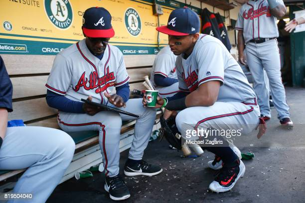 Third Base Coach Ron Washington of the Atlanta Braves goes over notes with Johan Camargo in the dugout prior to the game against the Oakland...
