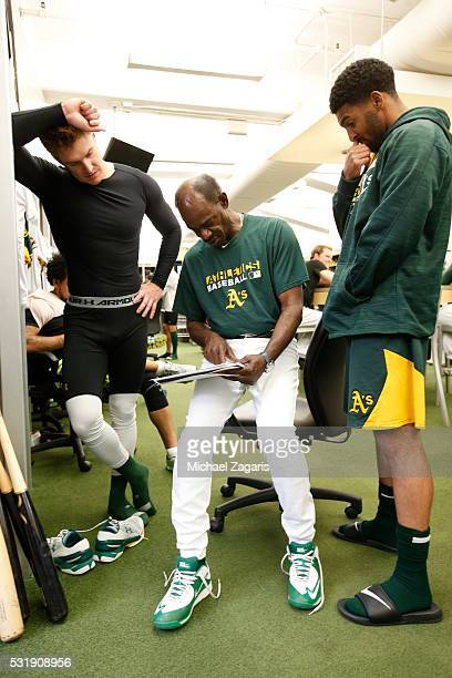 Third Base Coach Ron Washington of the Oakland Athletics goes over shifts with Mark Canha and Marcus Semien in the clubhouse prior to the game...