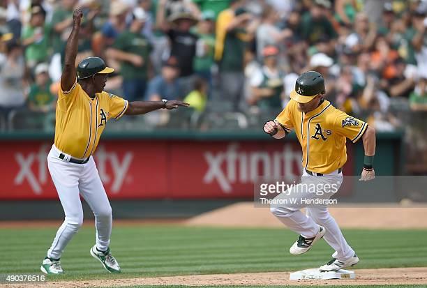 Third base coach Ron Washington of the Oakland Athletics waves Josh Reddick around third to score against the San Francisco Giants in the bottom of...