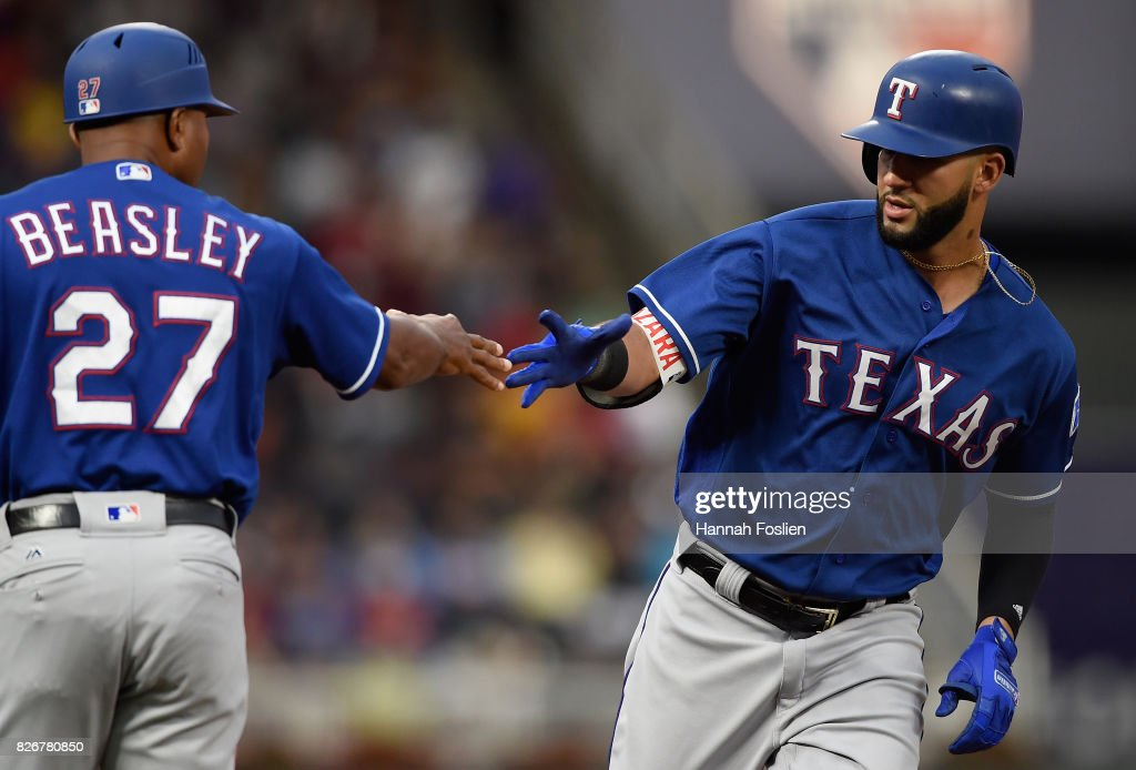 Third base coach Tony Beasley #27 of the Texas Rangers congratulates Nomar Mazara #30 a on two-run home run against the Minnesota Twins during the first inning of the game on August 5, 2017 at Target Field in Minneapolis, Minnesota.