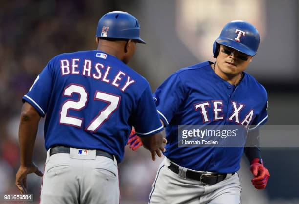 Third base coach Tony Beasley of the Texas Rangers congratulates ShinSoo Choo on a tworun home run against the Minnesota Twins during the fifth...