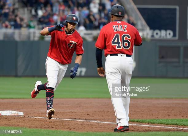 Third base coach Tony Diaz of the Minnesota Twins congratulates Eddie Rosario on a solo home run against the Chicago White Sox during the third...