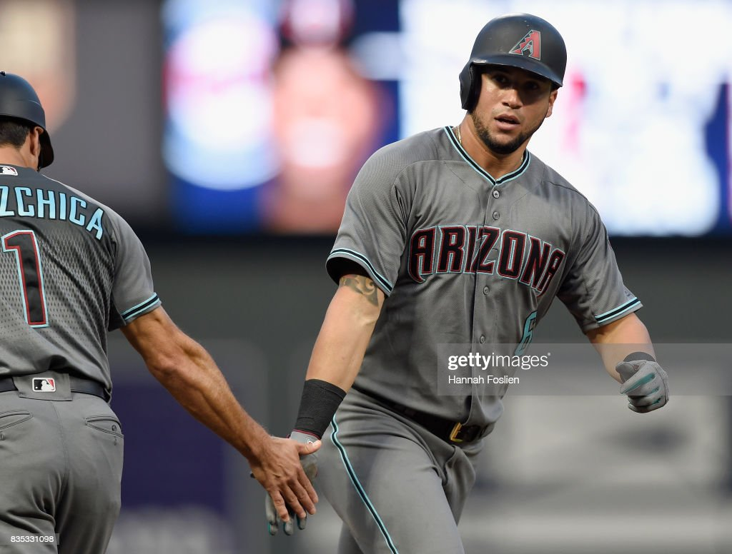 Third base coach Tony Perezchica #1 of the Arizona Diamondbacks congratulates David Peralta #6 on a solo home run against the Minnesota Twins during the second inning of the game on August 18, 2017 at Target Field in Minneapolis, Minnesota.