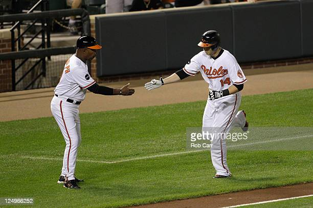 Third base coach Willie Randolph congratulates Nolan Reimold of the Baltimore Orioles after hitting a solo home run against the Tampa Bay Rays during...