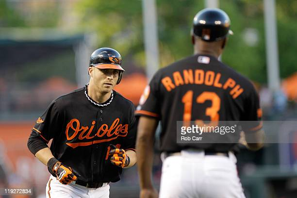 Third base coach Willie Randolph waits to congratulate Nolan Reimold of the Baltimore Orioles after hitting a solo home run against the Cleveland...