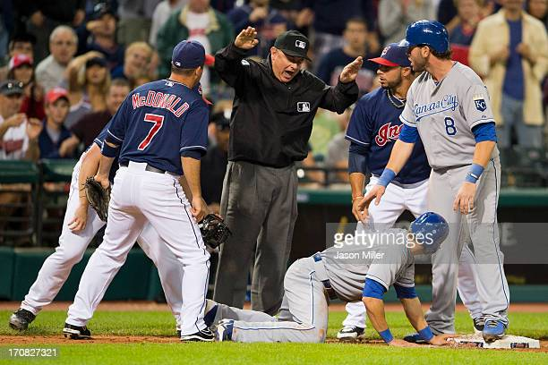 Third base umpire Greg Gibson calls David Lough safe after a run down where closing pitcher Vinnie Pestano tags out Mike Moustakas of the Kansas City...