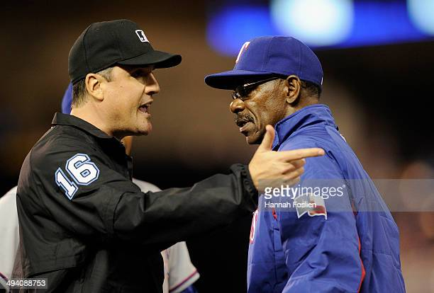 Third base umpire Mike DiMuro speaks with manager Ron Washington of the Texas Rangers after Eduardo Nunez of the Minnesota Twins was called safe at...