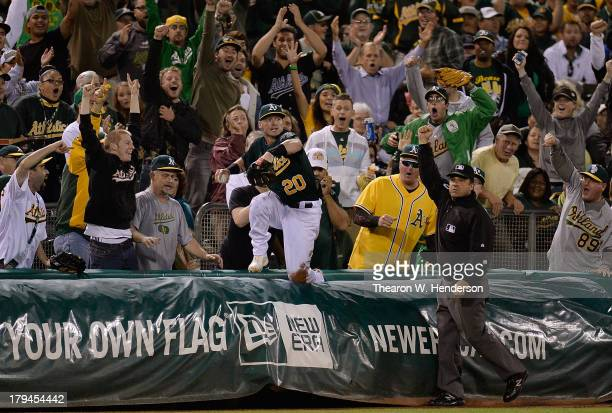 Third base umpire Phil Cuzzi raises his arm with the out sign after Josh Donaldson of the Oakland Athletics dove over the tarp catching a foul ball...