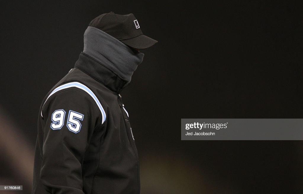 Third base umpire Tim Timmons #95 tries to stay warm as the Colorado Rockies host the Philadelphia Phillies in Game Three of the NLDS during the 2009 MLB Playoffs at Coors Field on October 11, 2009 in Denver, Colorado.