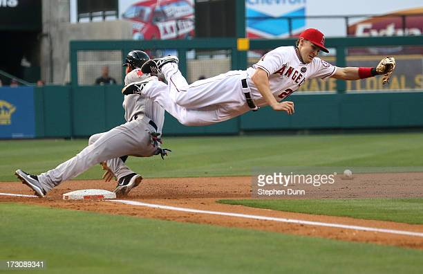 Third baseman Brendan Harris of the Los Angeles Angels of Anaheim can't reach a throw from catcher Chris Ianetta as jacooby Ellsworth of the Boston...