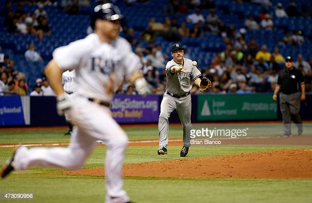 Third baseman Chase Headley of the New York Yankees tosses to first base on a single by Logan Forsythe of the Tampa Bay Rays during the fifth inning...