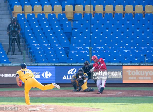 Third baseman Chi Hung Liu of Wei Chuan Dragons hiting with zero audience at the court during the CPBL preseason game between CTBC Brothers and Wei...