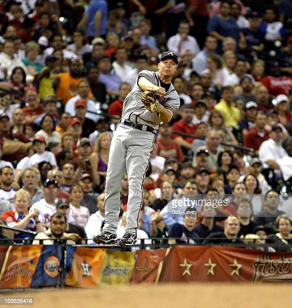 Third baseman Chipper Jones of the Atlanta Braves throws out Hunter Pence of the Houston Astros from deep behind the base at Minute Maid Park on...
