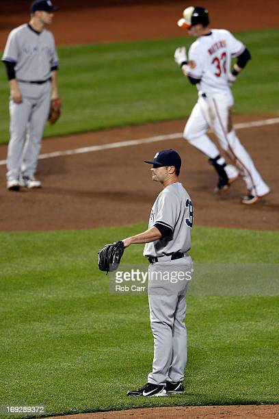 Third baseman David Adams and pitcher Preston Claiborne of the New York Yankees look on as Matt Wieters of the Baltimore Orioles jogs the bases after...