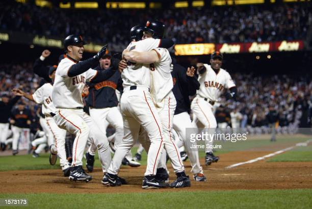 Third baseman David Bell of the San Francisco Giants hugs shortstop Rich Aurilia at home plate after scoring the gamewinning run to end game five of...