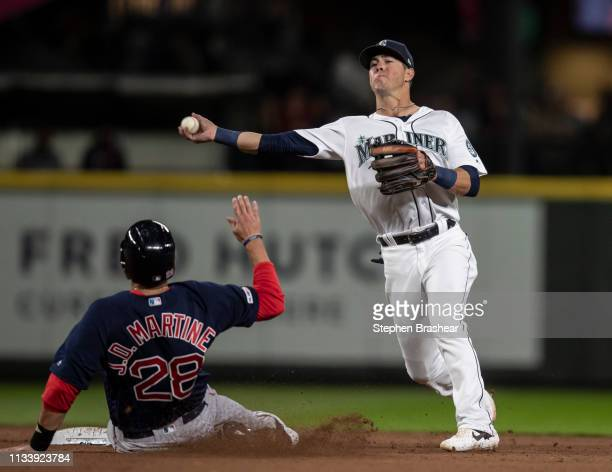 Third baseman Dylan Moore of the Seattle Mariners turns a double play after forcing out JD Martinez of the Boston Red Sox at second base on a ball...