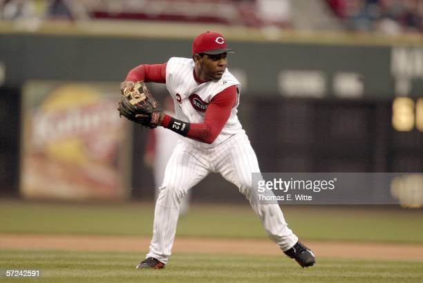 Third Baseman Edwin Encarnacion of the Cincinnati Reds scoops up a bunt and hurls towards first base against the Chicago Cubs on Opening Day at Great...