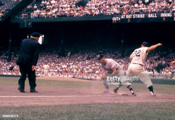 Third baseman Granny Hamner of the Cleveland Indians misses the tag as Bobo Osborne of the Detroit Tigers reaches third base as umpire Bill Summers...