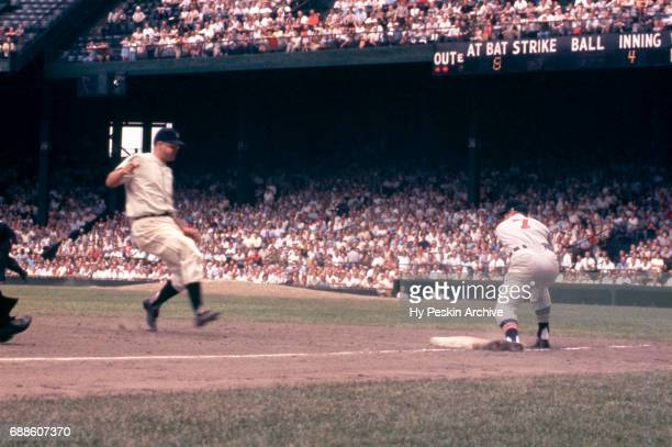 Third baseman Granny Hamner of the Cleveland Indians waits for the throw as Bobo Osborne of the Detroit Tigers goes for third base during an MLB game...