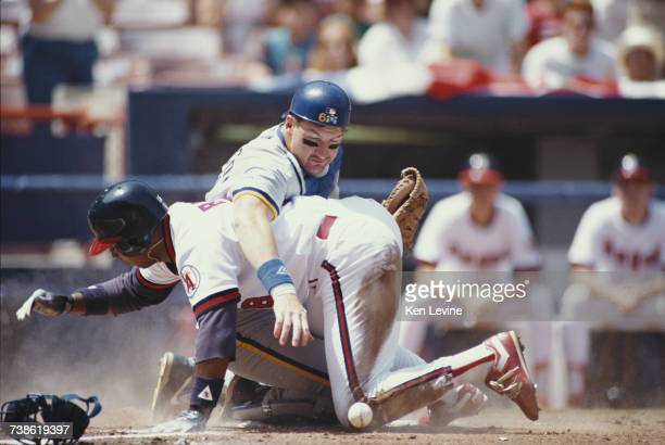Third baseman Hubie Brooks of the California Angels forces catcher Andy Allanson of the Milwaukee Brewers to drop the ball as he slides into home...