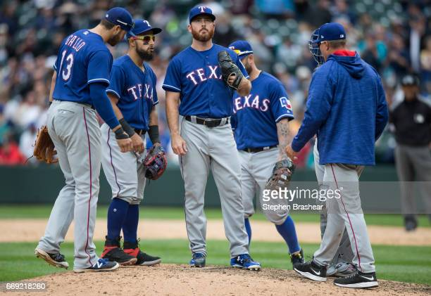 third baseman Joey Gallosecond baseman Rougned Odor relief pitcher Sam Dyson Mike Napoli and manager Jeff Banister meet at the mound during the ninth...