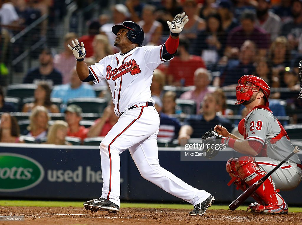 Third baseman Juan Uribe #2 of the Atlanta Braves hits a solo, go ahead home run in the seventh inning as catcher Cameron Rupp #29 of the Philadelphia Phillies looks on during the game at Turner Field on July 3, 2015 in Atlanta, Georgia.