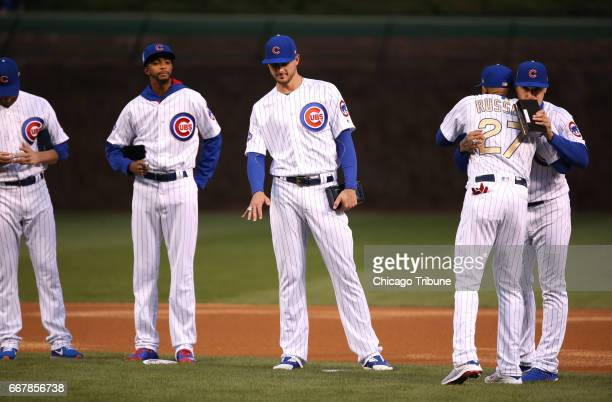 Third baseman Kris Bryant looks at his ring as shortstop Addison Russell receives a hug as members of the Chicago Cubs are presented with their 2016...