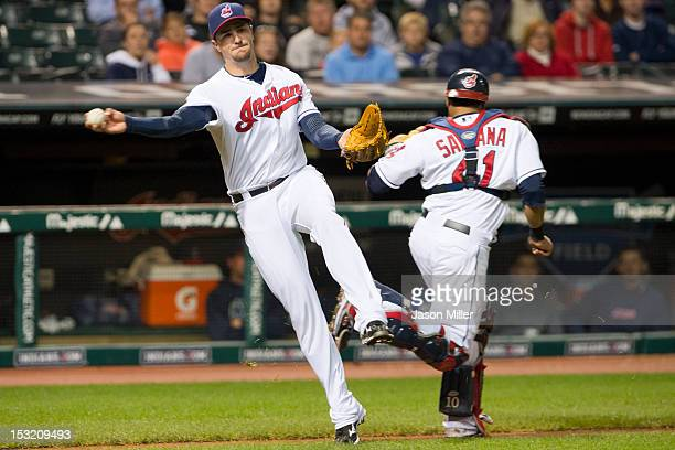 Third baseman Lonnie Chisenhall throws to first with back up from catcher Carlos Santana of the Cleveland Indians during the sixth inning against the...