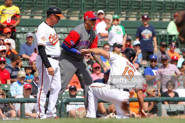 Third baseman Manny Machado of the Dominican Republic helps up regular season team mate Chris Davis of the Orioles after tagging him out for the...