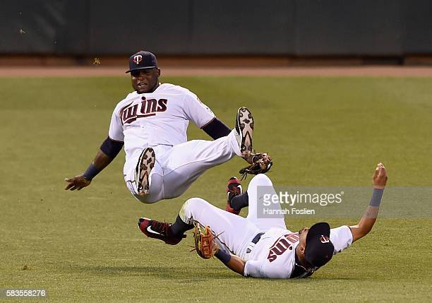 Third baseman Miguel Sano of the Minnesota Twins trips over teammate and right fielder Eddie Rosario after making a catch of the ball hit by Freddie...