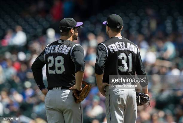 Third baseman Nolan Arenado of the Colorado Rockies and starting pitcher Kyle Freeland of the Colorado Rockies meet at the pitcher's mound during a...