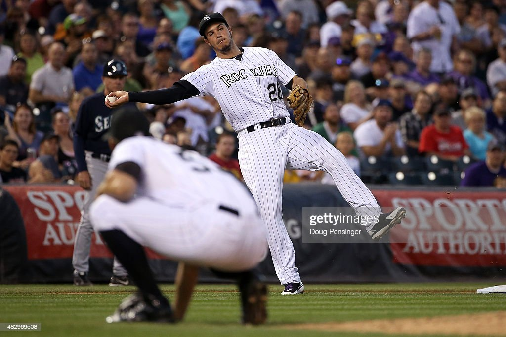 Third baseman Nolan Arenado #28 of the Colorado Rockies fields a ground ball by Nelson Cruz #23 of the Seattle Mariners as pitcher Christian Friedrich #53 of the Colorado Rockies avoids the throw for an out in the fifth inning during interleague play at Coors Field on August 4, 2015 in Denver, Colorado.