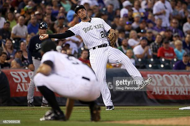Third baseman Nolan Arenado of the Colorado Rockies fields a ground ball by Nelson Cruz of the Seattle Mariners as pitcher Christian Friedrich of the...