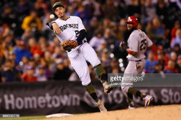 Third baseman Nolan Arenado of the Colorado Rockies makes a throw on the run to first base for the third out of the ninth inning as Dexter Fowler of...